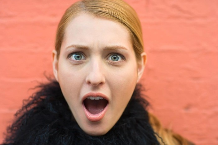 Person with surprised expression, against a flamingo-pink wall.