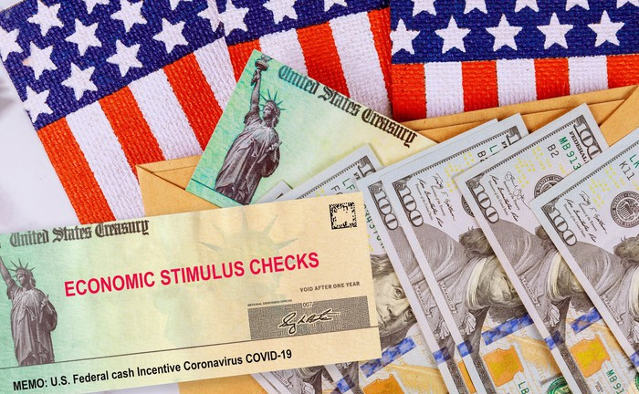 An economic stimulus check and hundred dollar bills on top of American flags.