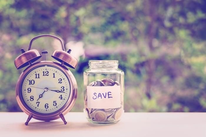 Alarm clock next to a savings jar.