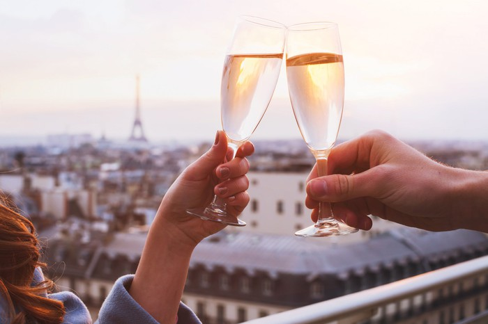 Two people clink  champagne glasses with a view of Paris in the background.