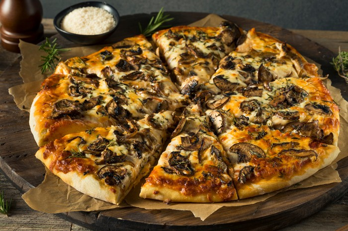 Mushroom pizza cut into eight slices, with a saucer of grated cheese beside it.