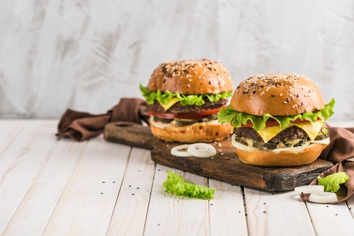 A pair of premium burgers on a cutting board.