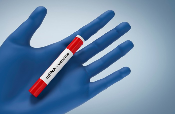 mRNA vaccine printed on the label of a vial held in a gloved hand.