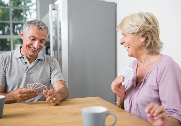 Smiling older man and woman playing cards