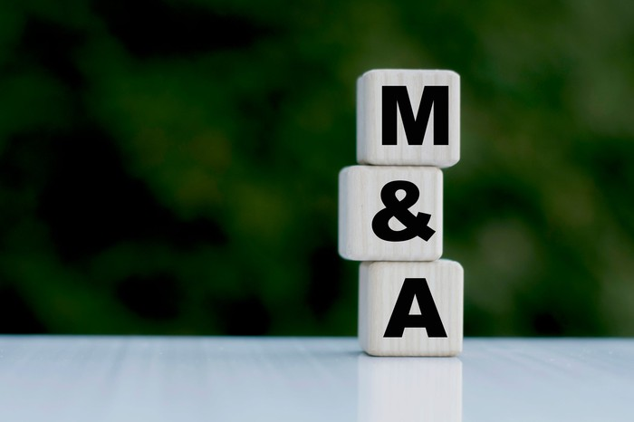 Blocks with the letters M&A stacked atop each other. M&A stands for mergers and acquisitions.