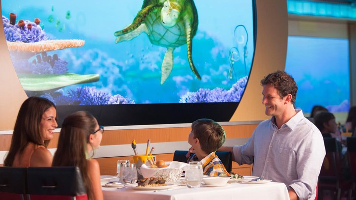 A family at a Disney cruise ship dining room with animated screens.