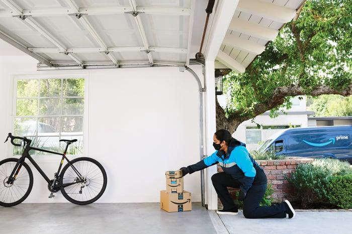 Woman placing Amazon.com boxes inside garage