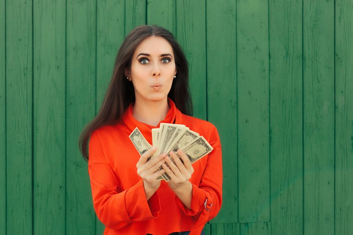 A woman holding a stack of dollar bills.