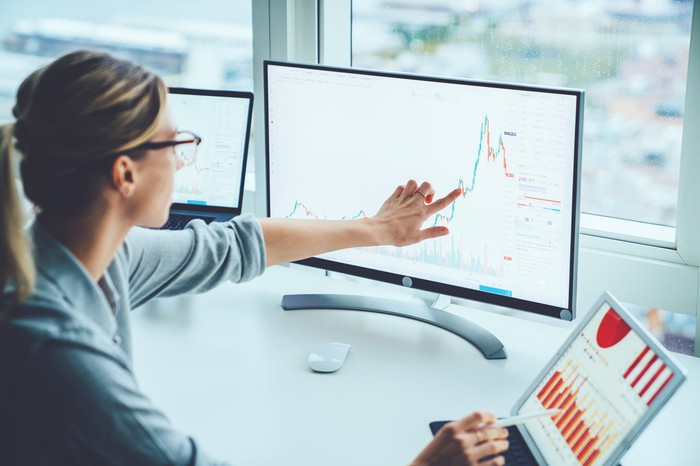 Woman pointing to graphs on computer screens