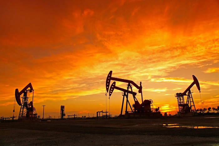 Several oil wells under a setting sun.
