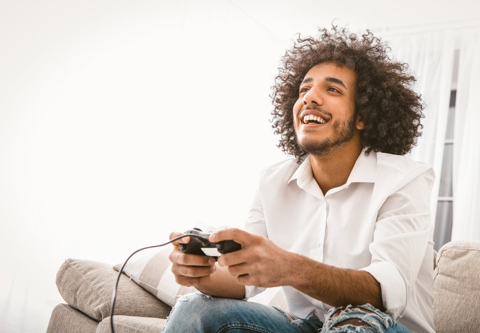 A man holding a controller while playing a video game.