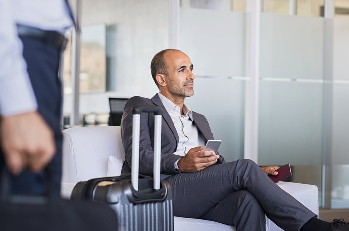 Man wearing suit and holding his smartphone while sitting next to his luggage