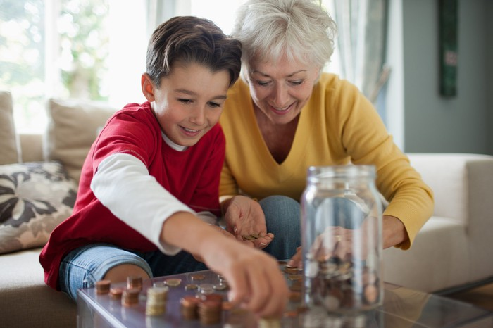 Grandmother and her grandson counting coins together.
