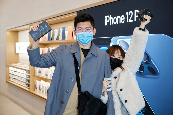 Customers holding up boxed iPhones at the Apple Store Sanlitun
