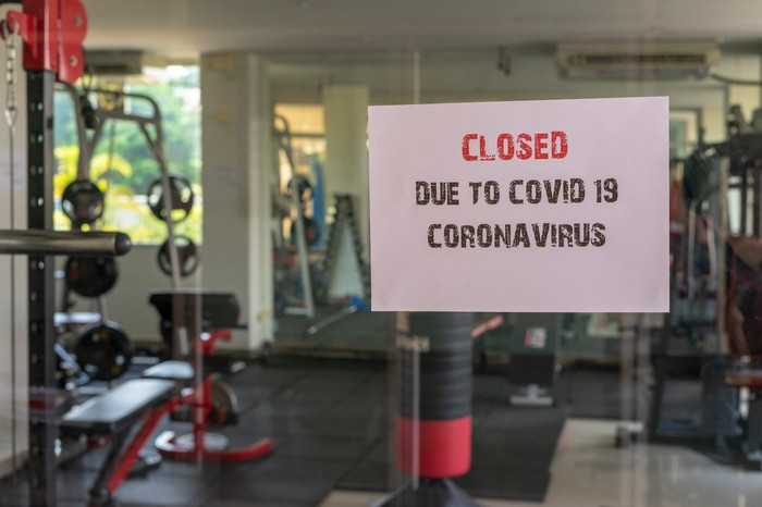 Glass gym wall with sign on it saying it's closed due to COVID-19, with gym machines and equipment visible inside