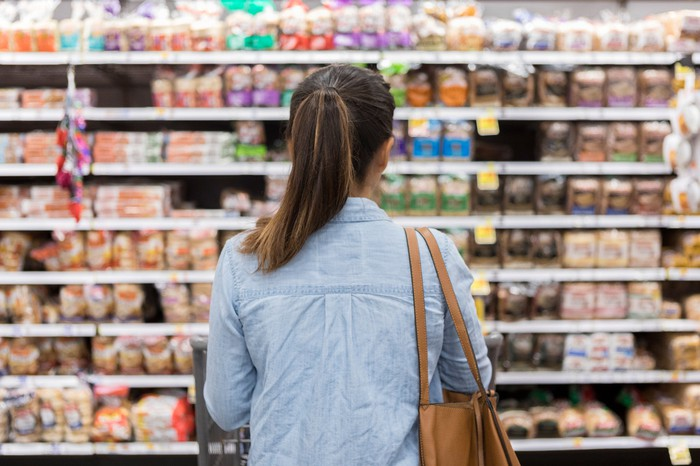 Woman browsing a grocery store aisle.