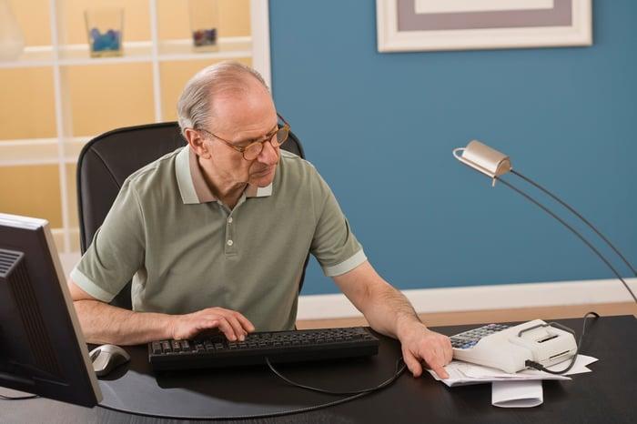 Older man at desk typing on computer keyboard