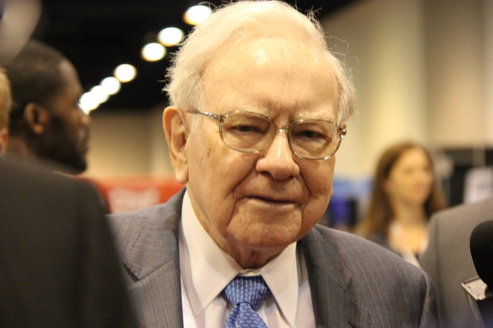 Warren Buffett with people in the background.