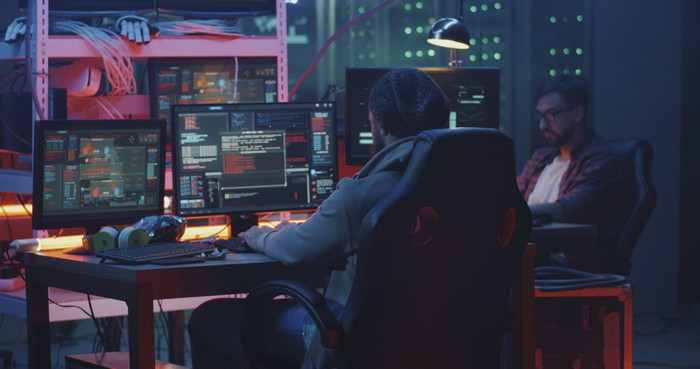 Two hackers seated at a desk and working.