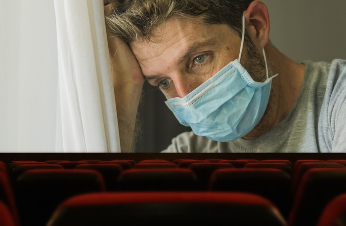 In an empty movie theater, the silver screen shows a tired person wearing a surgical face mask.