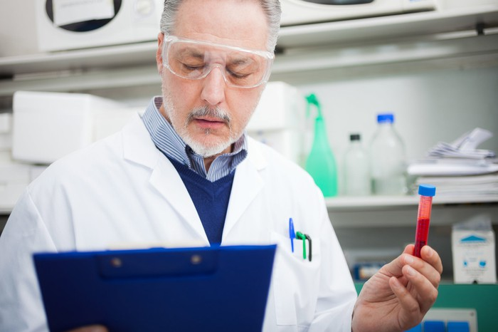 A lab researcher reading a clipboard while holding up a vial of red liquid in his left hand.