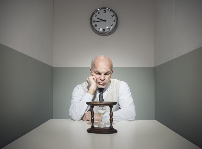 Man sitting in a small room watching an hourglass empty.