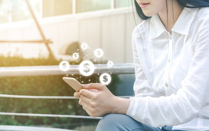 Woman on smartphone with dollar signs above it