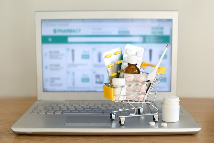 A miniature shopping cart filled with prescription drugs sits on atop a laptop displaying an online pharmacy