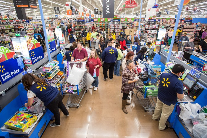 Shoppers at Walmart checkouts with racks of merchandise in the background.