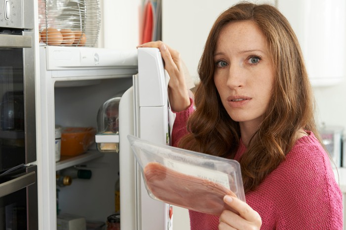 Woman holding a package of sliced meats as she holds the refrigerator door open.