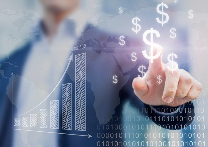 Man in suit touching digital dollar signs, with bar chart showing growth