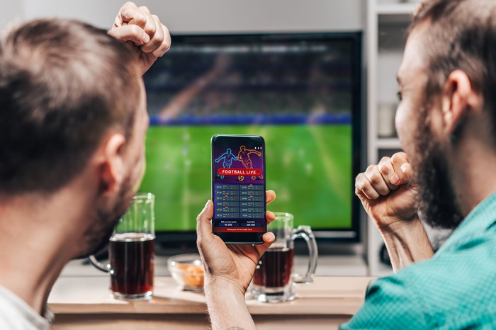 Two men watching a football game while one holds up a smartphone with a sports betting app open on it.