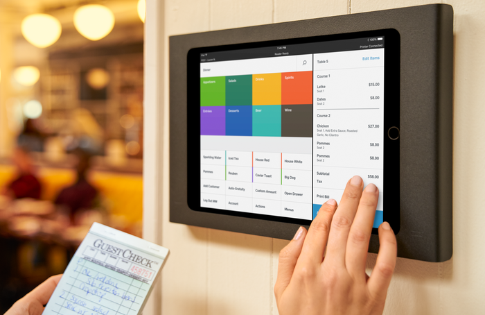 A restaurant worker using Square's services on a wall-mounted terminal.