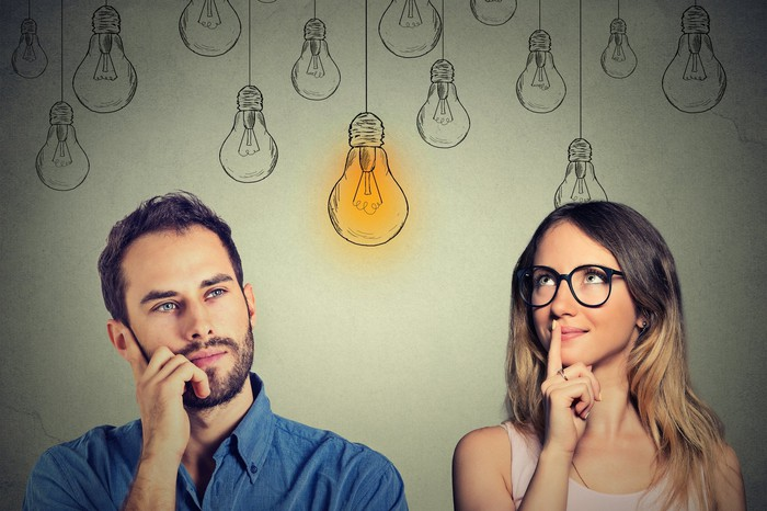 Young man and woman standing side by side in thought with illustrations of light bulbs above their heads.