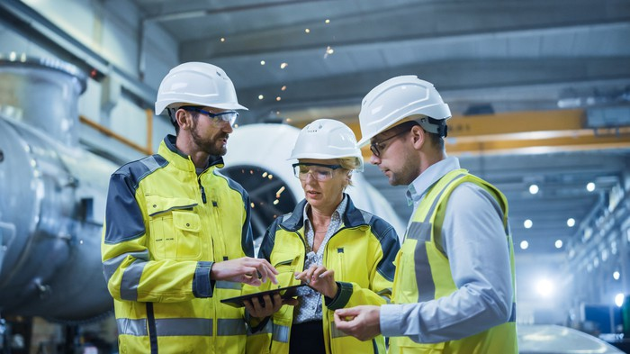 Three Heavy Industry Engineers Discussing in Pipe Manufacturing Factory.