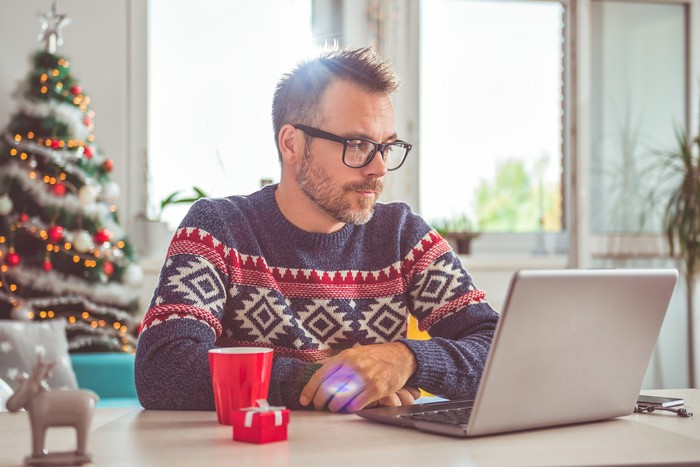 Man in festive sweater studying a laptop screen with a Christmas tree behind him in the background.