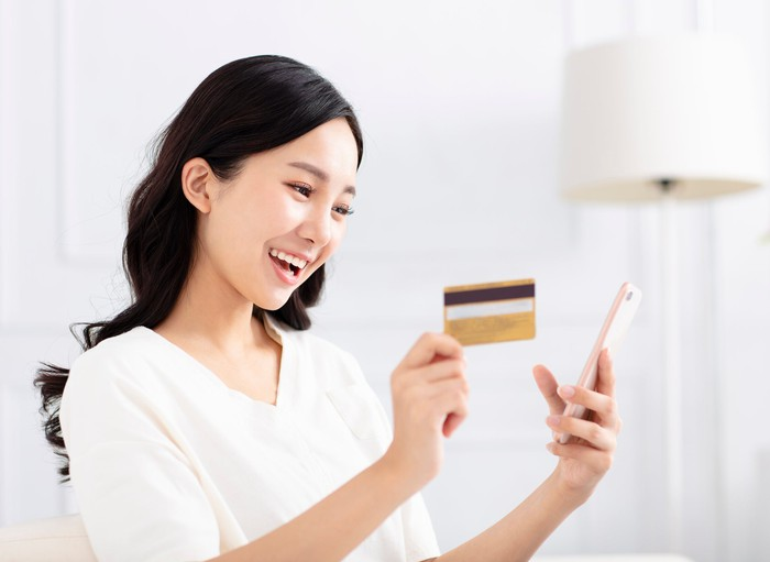 A young Asian woman smiles at her smartphone, holding a credit card in her other hand.