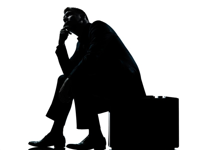 Silhouette of a businessman sitting on his briefcase, seemingly in deep thought.