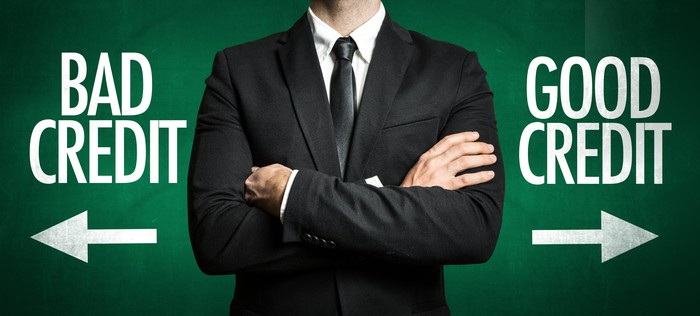 Man in suit stands with arms crossed with pictures that read BAD CREDIT and GOOD CREDIT on either side of him.