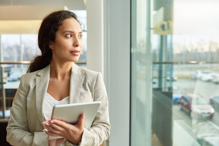 A woman dressed in business attire holding a tablet and looking out a window.