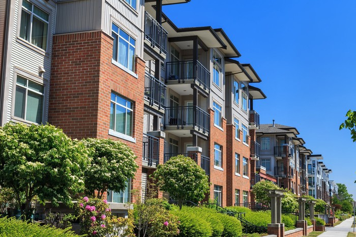 A large brick, multi-story apartment or condo building.