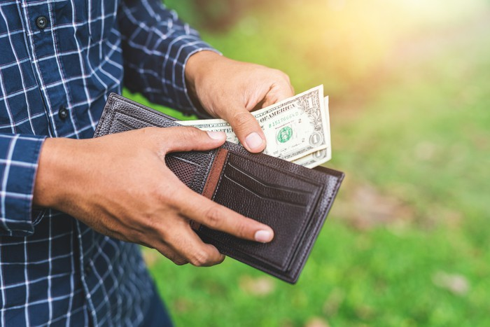 Man pulling one dollar bills from a leather wallet.