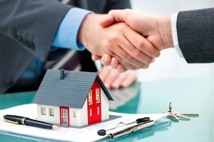 Two men shake hands over a clipboard with paperwork, keys, and a miniature model house.
