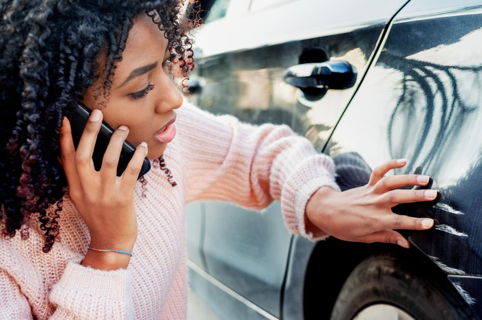 Woman on a smartphone looking at damage to her car.