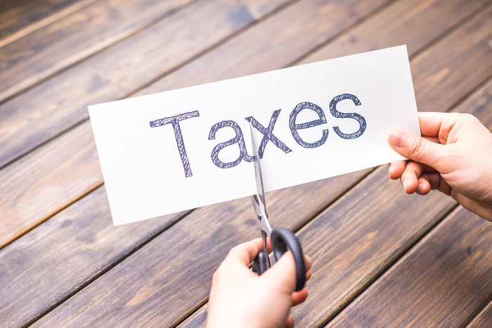 A person cutting a piece of paper with the word Taxes written on it.