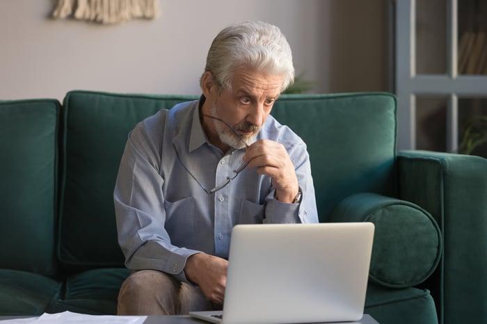 Older man looking upset in front of laptop