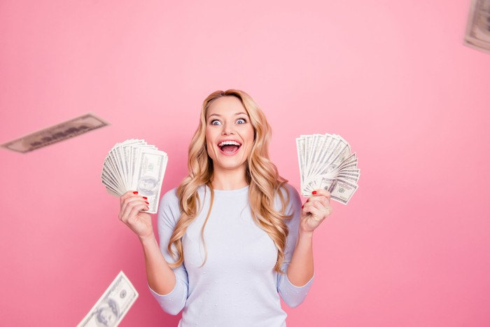 An excited woman throwing money into the air against a pink background.