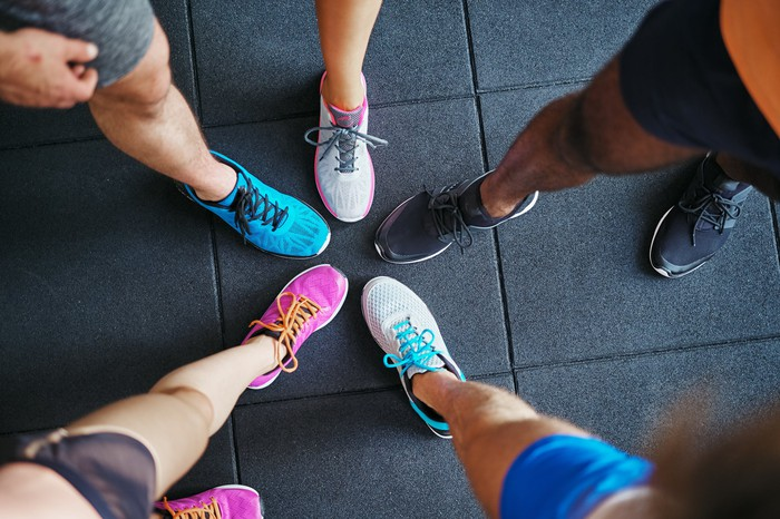 Picture of five people standing together wearing different athletic shoes.