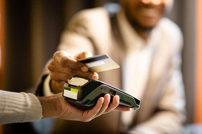 Man holding credit card above card terminal to make a payment