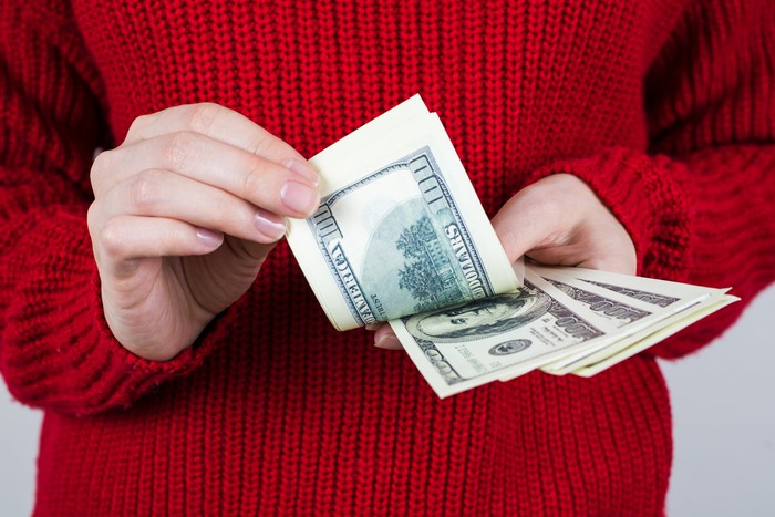 A woman's hands hold out a handful of hundred dollar bills.